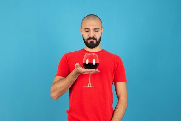 青い壁に赤ワインのグラスを保持している魅力的な若い男。