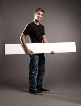 Attractive young man holding a white banner on a gray