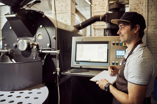 클립 보드를 들고 전문 커피 로스팅 장비의 제어판에 서있는 동안 웃고 앞치마에 매력적인 젊은 남자