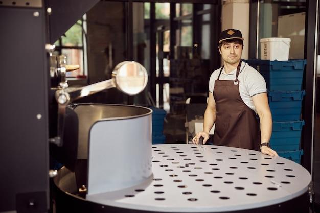 전문 커피 로스팅 장비에 서있는 동안 심각한 표정으로 멀리 찾고 앞치마에 매력적인 젊은 남자