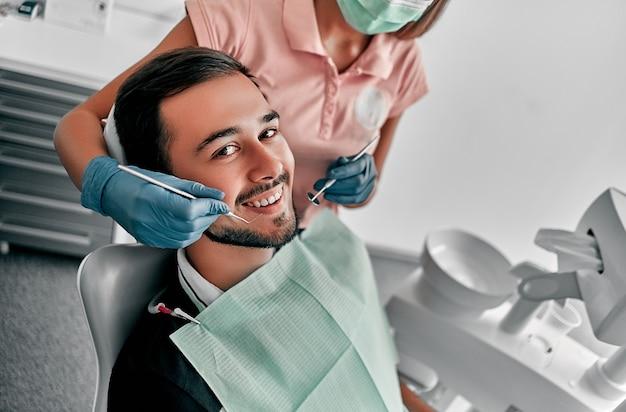 여성 치과 의사와 구강 클리닉에서 매력적인 젊은 남자. 건강한 치아 개념입니다.