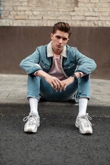 トレンディな白いスニーカーで破れたファッショナブルなブルージーンズのスタイリッシュなデニムジャケットの魅力的な若い男は、街の道路の近くの歩道で休んでいます。通りでファッションカジュアルな服を着たハンサムな男。