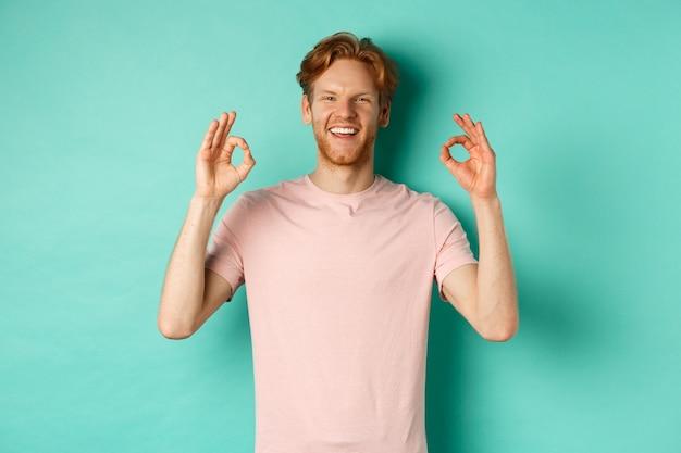 T- 셔츠 미소에 매력적인 젊은 남자는 만족, 승인에 고개를 끄덕이고 확인 서명을 보여주는, 승인하고 청록색 배경 위에 서있는 멋진 무언가에 동의합니다.