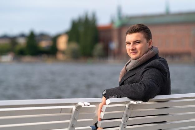 Привлекательный молодой человек в теплом пальто и шарфе сидит на скамейке на открытом воздухе с видом на неспокойную воду, поворачиваясь, чтобы улыбнуться в камеру