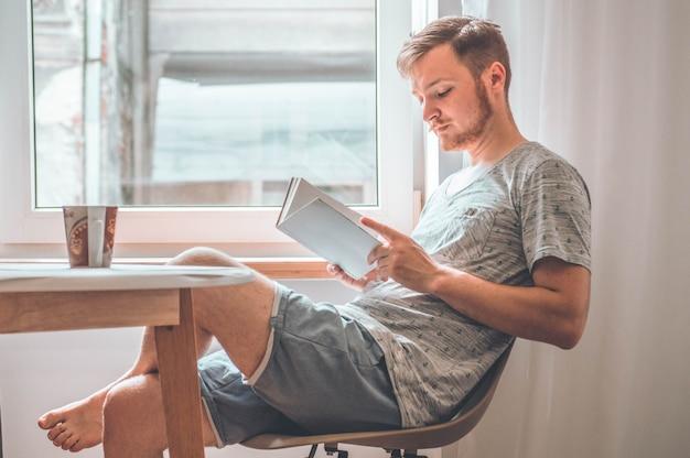 魅力的な若い男は家で本を読んでいます