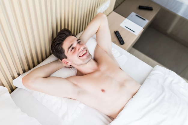 Attractive young man is sleeping in his bed.
