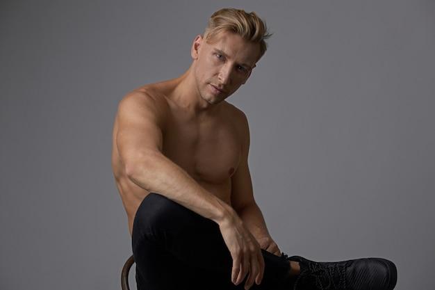 Привлекательный молодой человек позирует с голым торсом, сидя на стуле