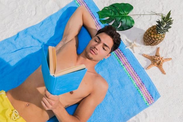 魅力的な若い男がビーチで本を読んで