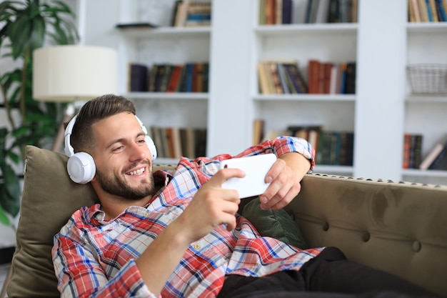 Attractive young man relaxing on a couch at home, listening music and playing on smartphone.
