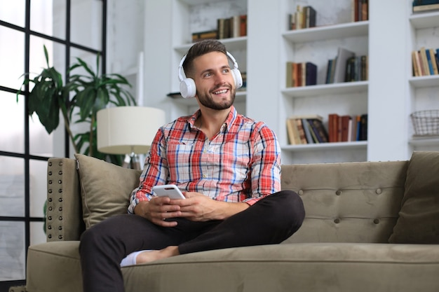 Attractive young man relaxing on a couch at home and using mobile phone for cheking social nets.
