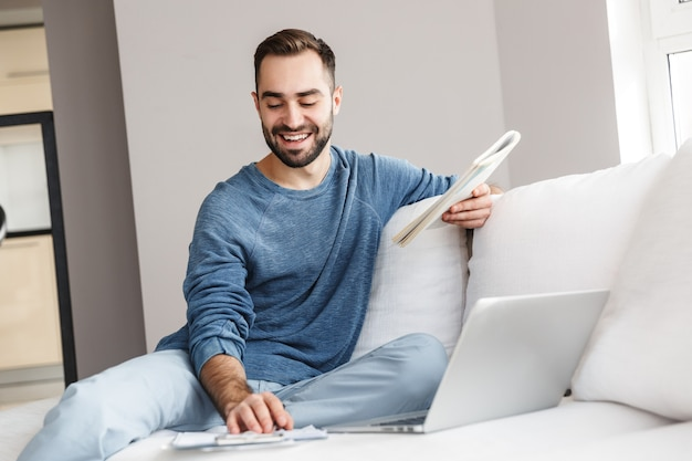 Attractive young man relaxing on a couch at home, working with laptop computer and documents