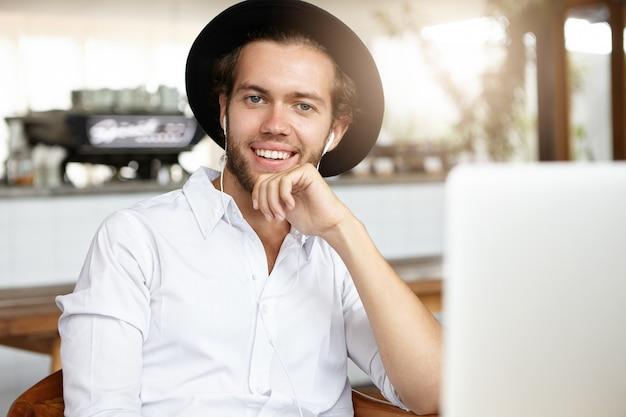 매력적인 젊은 남자가 현대적인 카페에서 점심 시간 동안 편안하고 열린 노트북 앞에 앉아 이어폰에서 온라인으로 재미있는 비디오를 보면서 행복하게 웃고 있습니다.