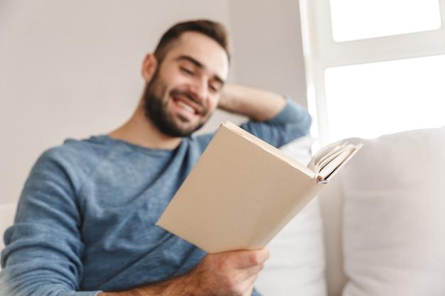 Привлекательный молодой человек отдыхает на диване у себя дома, читая книгу