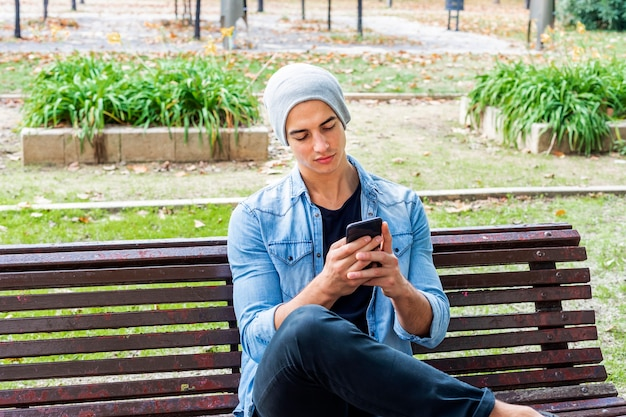 An attractive young man sitting on a bench outside using his cell phone wearing a hat