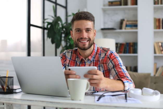 Attractive young man sitting at desk at home office and using mobile phone for cheking social nets.