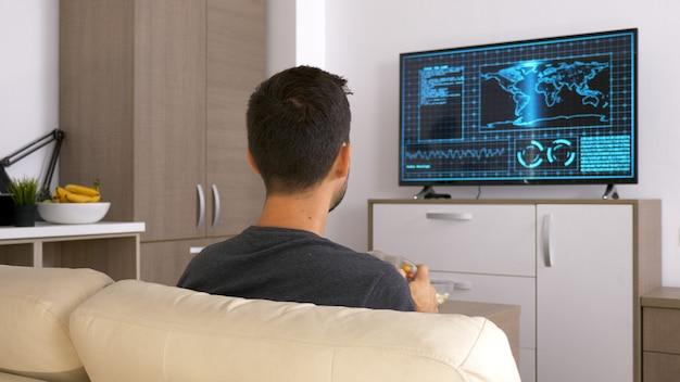 그의 소파에 앉아서 비디오 게임을 하는 매력적인 젊은 남자. 집에 있는 것이 편안합니다.