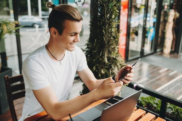 매력적인 젊은 남자가 미소하고 노트북 근처 야외 카페에서 테이블에 앉아있는 동안 현대 태블릿을 탐색