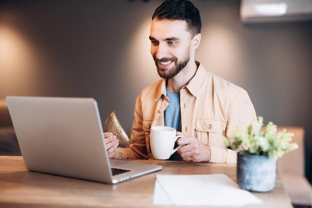 Привлекательный молодой человек улыбается, используя свой современный ноутбук и разговаривает по видеосвязи
