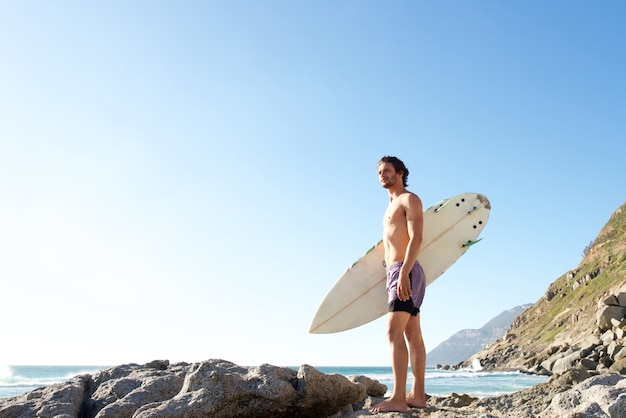 Attractive young man standing on beach carrying surfboard