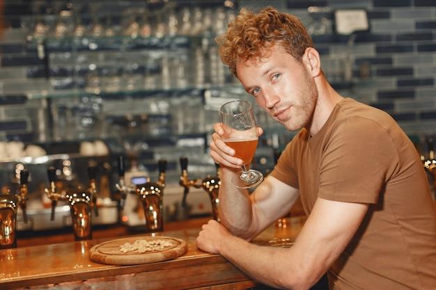 바 뒤에 서있는 매력적인 젊은 남자. 갈색 티셔츠를 입은 남자는 손에 유리 잔을 든다.