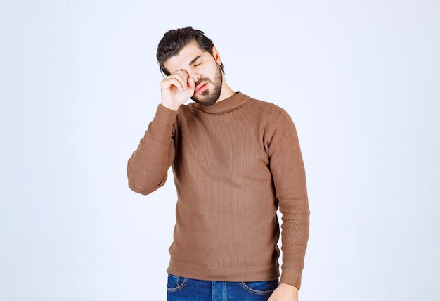 An attractive young man standing and covering his eye with fist.