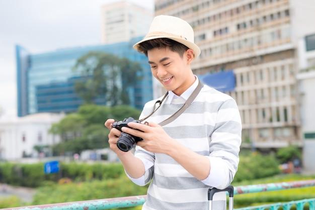 매력적인 젊은 남자, 학생 또는 프리랜서 사진가는 미소를 지으며 카메라를 향해 웃는다