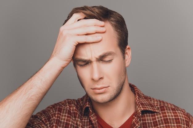 Привлекательный молодой человек страдает от сильной головной боли