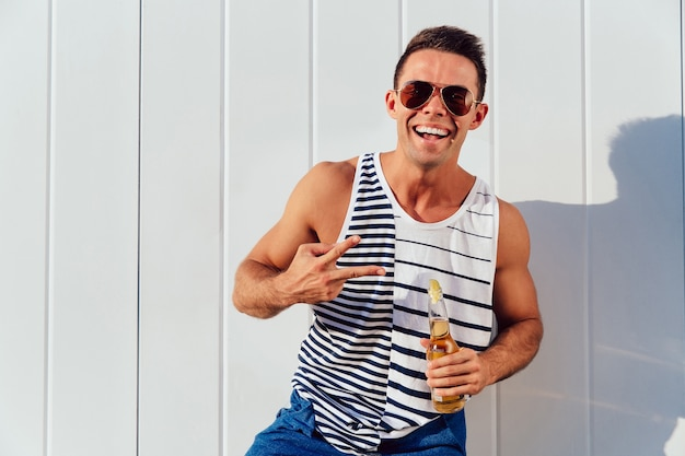 Attractive young man in sunglasses showing two fingers, peace gesture