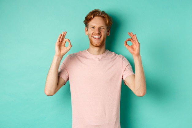 Attractive young man in t-shirt smiling satisfied, nod in approval and showing ok sign, approve and agree with something cool, standing over turquoise background.