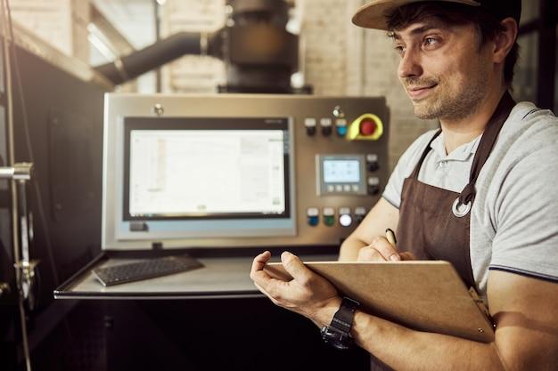 매력적인 젊은 남자가 메모를하고 커피 로스팅 기계의 제어판 근처에 서있는 동안 웃고