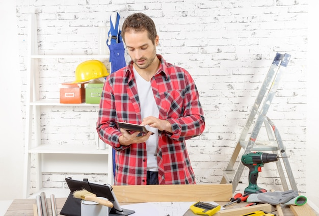 Attractive young man using the tablet for diy