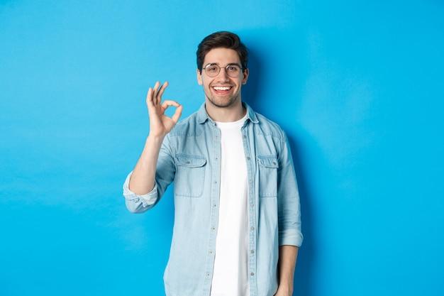 眼鏡とカジュアルな服を着て、青い背景に立って、何かのように、承認の良いサインを示している魅力的な若い男