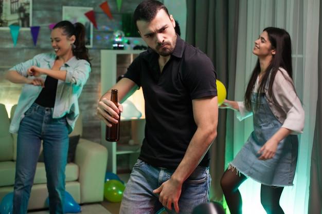 友達とのパーティーで踊る彼の手にビール瓶を持つ魅力的な若い男。風船を持っている女の子。
