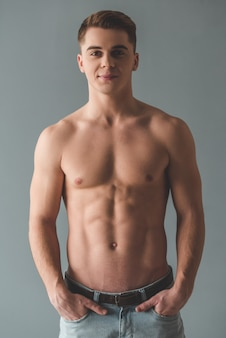 Attractive young man with bare torso is looking at camera.