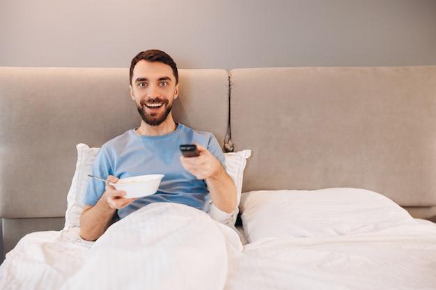 Привлекательный молодой человек с бородой завтракает в постели и выглядит счастливым во время просмотра телешоу