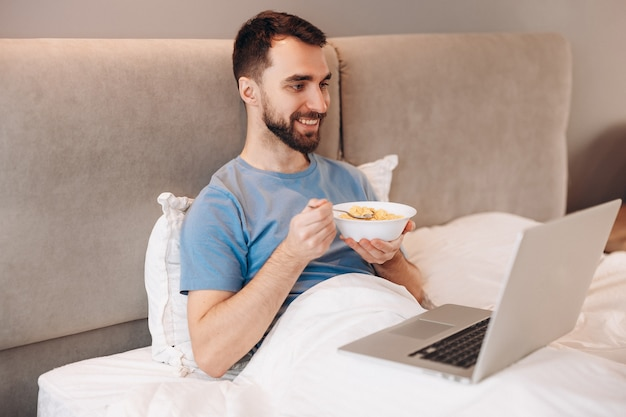ノートパソコンの前のベッドで朝食を食べて笑っているひげを持つ魅力的な若い男