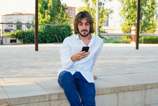 Attractive young man with beard, with white shirt looks at his smartphone in the park.