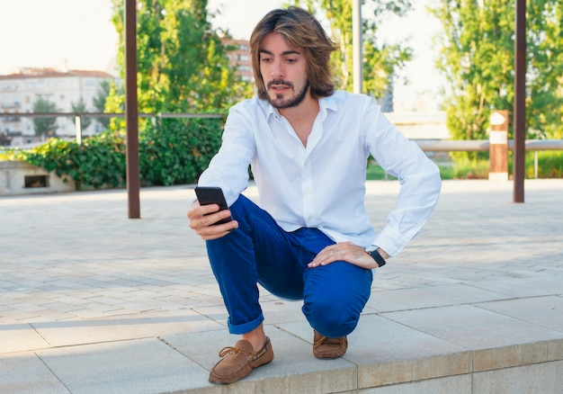 Attractive young man with beard, with white shirt looks at his smartphone with serious face in the park.