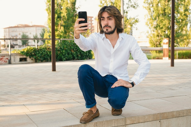 Attractive young man with beard, with white shirt makes himself a selfie with serious face in the park.