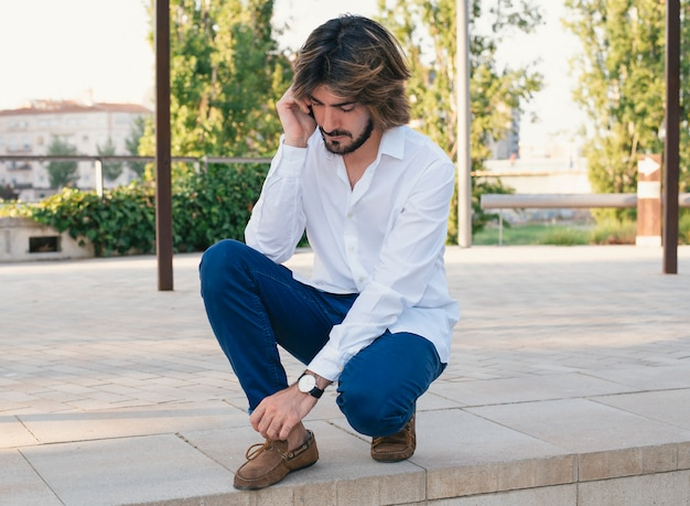 Attractive young man with beard, with white shirt talks to his smartphone.