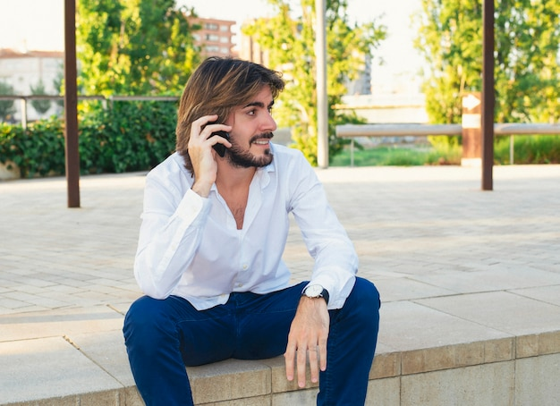 Attractive young man with beard, with white shirt who is in the park smiles while talking on the smartphone.