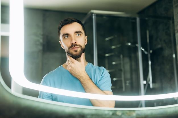 Привлекательный молодой человек с голубыми глазами, касаясь его бороды перед зеркалом утром