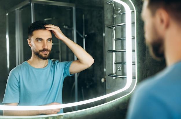 Привлекательный молодой человек с голубыми глазами, касаясь его волос перед зеркалом утром