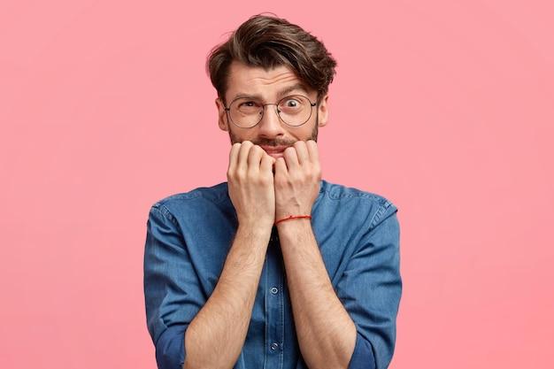 Привлекательный молодой человек с растерянным нервным выражением лица, кусает ногти, боится совершить ужасную ошибку, чувствует беспокойство, выглядит смущенным, носит джинсовую рубашку, изолирован на розовой стене