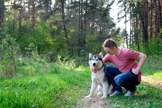 Attractive young man with his dog malamute on a walk in the forest