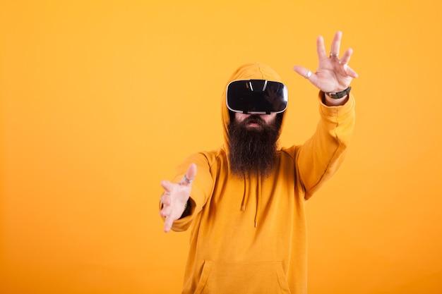 노란색 배경 위에 손짓을 하는 가상 현실 헤드셋을 쓰고 긴 수염을 가진 매력적인 젊은 남자. 현대 비전. 잘 생긴 남자. 노란색 후드티.
