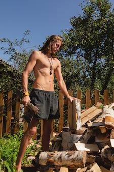 Привлекательный молодой человек с длинными волосами и солнцезащитными очками рубит дрова в красивом саду в деревне в солнечный день.