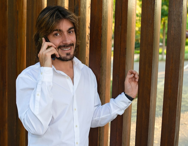 Attractive young man with long hair and beard, dressed in white shirt talking through his smarthpone on the street, looks at the camera smiling.