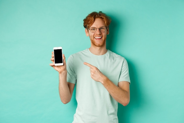 Attractive young man with red beard and hair pointing finger at blank smartphone screen, showing online promotion or app, smiling at camera, turquoise background.