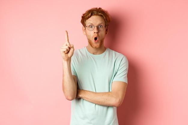 Attraente giovane con i capelli rossi, alzando il dito nel gesto di eureka e lanciando all'idea, in piedi su sfondo rosa